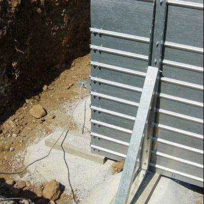 Posa dei blocchi di sostegno perimetrali e fissaggio struttura metallica in acciaio nervato autoportante con contrafforti